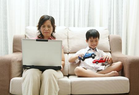 carritos de juguete: Madre que usa el ordenador port�til e hijo jugando coches de juguete