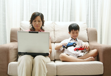 toy cars: Mother using laptop and son playing toy cars LANG_EVOIMAGES