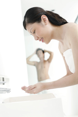 fair complexion: Woman washing her face while husband is taking a shower