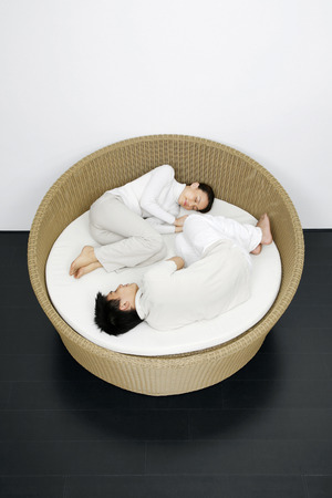 Woman and man curled up in a rattan bed