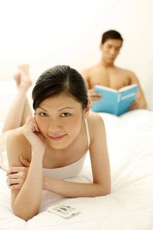 fair complexion: Woman watching TV while boyfriend is reading at the background LANG_EVOIMAGES