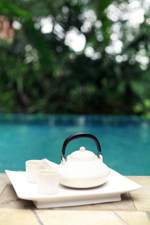 teacups: Teapot and teacups by the poolside