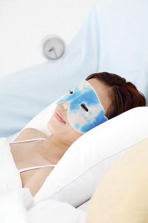 eye mask: Woman with eye mask lying on the bed