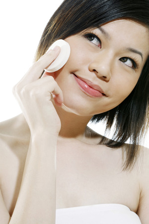 tube top: Woman applying compact powder on her face