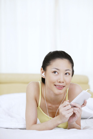 portable mp3 player: Woman lying on bed, listening to music on portable MP3 player LANG_EVOIMAGES