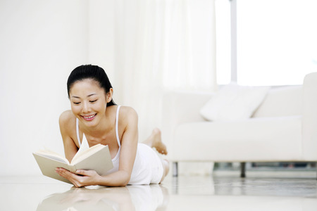 lying forward: Woman lying forward on the floor, reading book