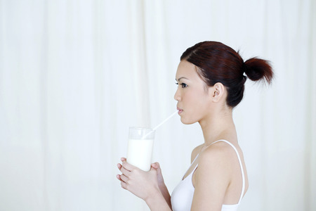 drinking straw: Donna che beve un bicchiere di latte con cannuccia