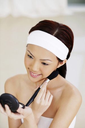 blusher: Woman applying blusher on her cheek LANG_EVOIMAGES
