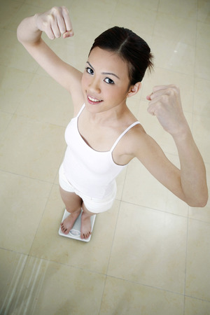 jubilating: Woman jubilating while standing on weight scale LANG_EVOIMAGES