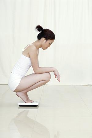 cuclillas: Mujer en cuclillas en la escala de peso