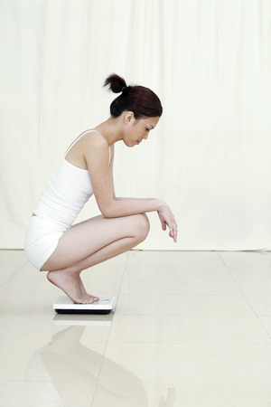 check ups: Woman squatting on weight scale LANG_EVOIMAGES