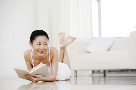 lying forward: Woman lying forward on the floor reading book