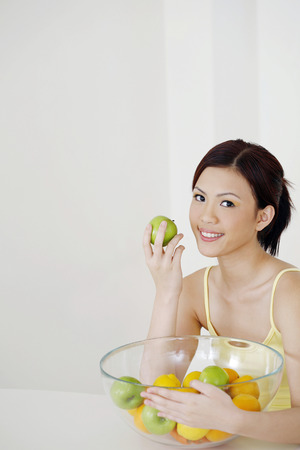 health conscious: Woman with a bowl of fruits LANG_EVOIMAGES