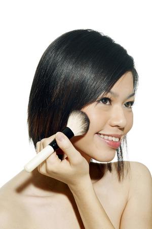 cheek to cheek: Woman applying blusher on her cheek LANG_EVOIMAGES
