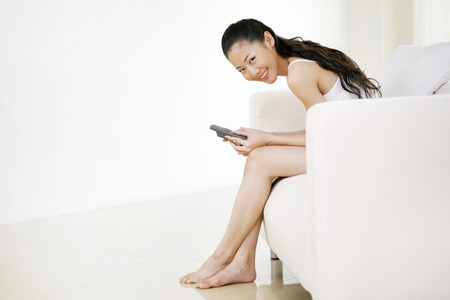 full grown: Woman smiling at the camera while text messaging on the mobile phone