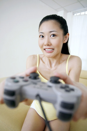playing video game: Woman playing video game console