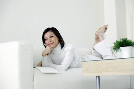 lying forward: Woman lying forward on the couch thinking