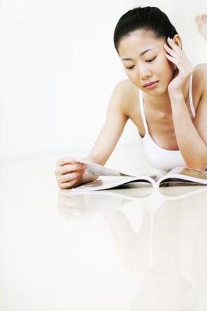 lying forward: Woman lying forward on the floor reading magazine LANG_EVOIMAGES