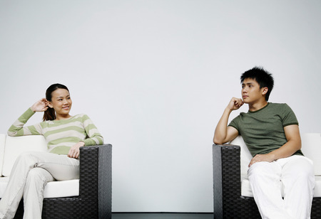 two person only: Man and woman sitting on couch, looking at each other LANG_EVOIMAGES