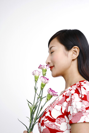smelling: Woman smelling flowers