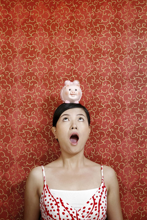 mouth opened: Woman with mouth opened, balancing a piggy bank on her head