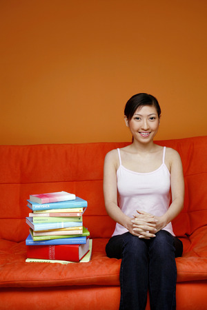 stacked books: Woman sitting on couch with stacked books beside her