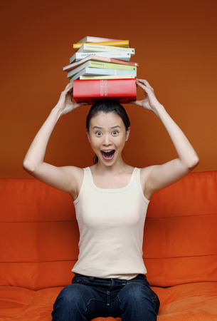 stacked books: Woman balancing stacked books on her head