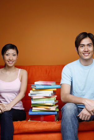 stacked books: Man and woman sitting on couch with stacked books in between