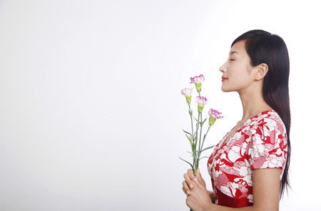 closing eyes: Woman closing eyes while smelling flowers LANG_EVOIMAGES