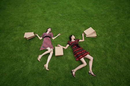 full grown: Women with paper bags lying on the field