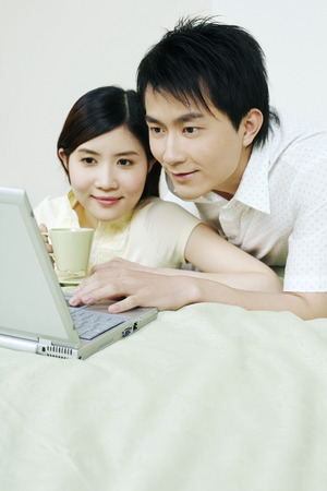 laying forward: Man and woman using laptop in the bedroom