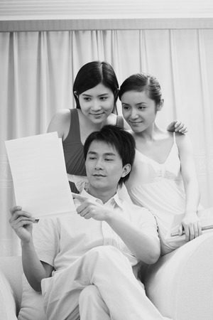 three people only: Man and two women looking at paper