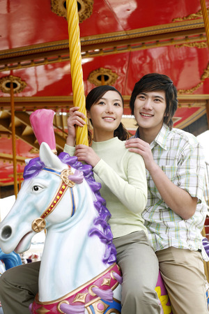 two persons only: Man and woman riding on carousel