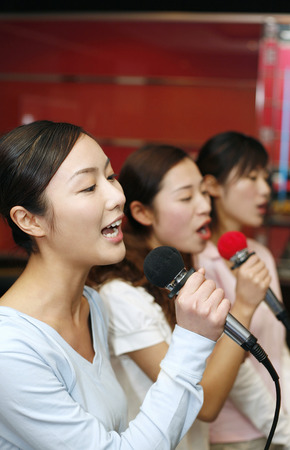 three people only: Women singing into microphones LANG_EVOIMAGES