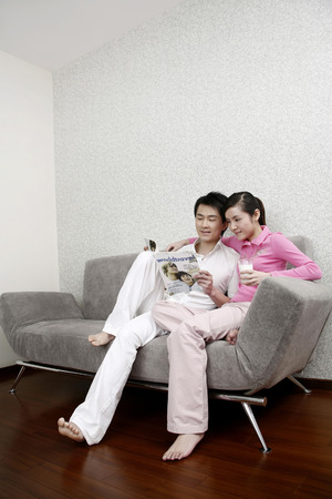 full grown: Man and woman reading magazine together