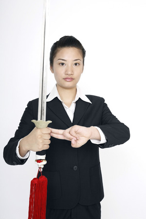 social grace: Businesswoman practising martial arts with a sword