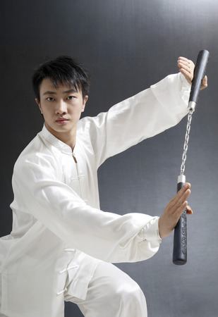 he is a traditional: Man with nunchaku striking a pose for the camera