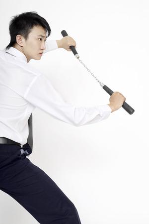 he is a traditional: Man with nunchaku striking a pose