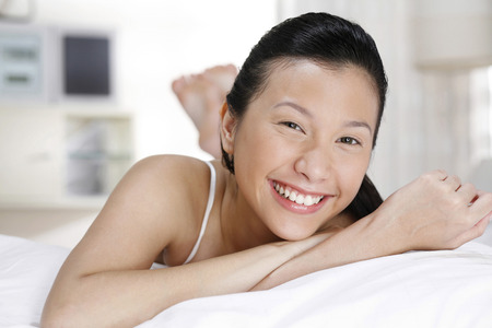 lying forward: Woman lying forward on the bed, smiling at the camera LANG_EVOIMAGES