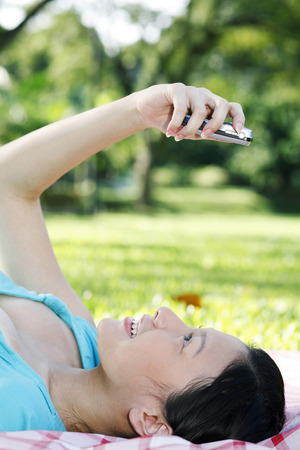 woman lying down: Woman lying down while looking at her mobile phone LANG_EVOIMAGES
