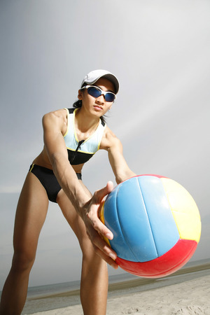 Woman picking up a volleyball Stock Photo