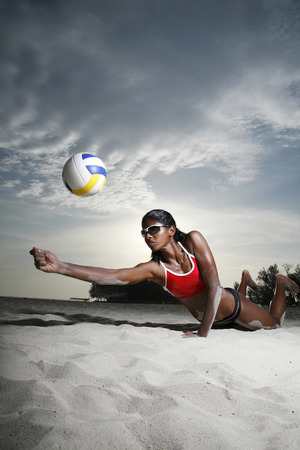 diving save: Woman diving to save a volleyball LANG_EVOIMAGES