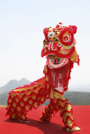 Performers in lion costume lifting the lion head