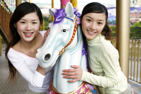 carousel horse: Women posing with carousel horse LANG_EVOIMAGES