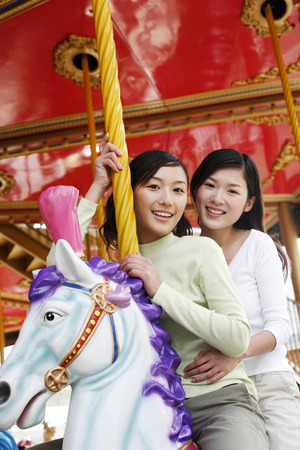 two persons only: Women riding on carousel LANG_EVOIMAGES