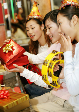 three people only: Woman opening present, friends watching LANG_EVOIMAGES