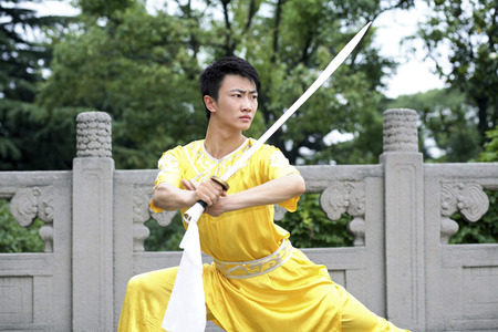 he is a traditional: Man practising martial arts with a sword LANG_EVOIMAGES