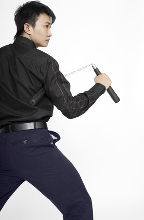 nunchaku: Businessman with nunchaku striking a pose for the camera