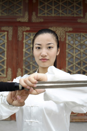 social grace: Woman with sword paying respect LANG_EVOIMAGES