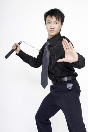 he is a traditional: Businessman with nunchaku striking a pose for the camera